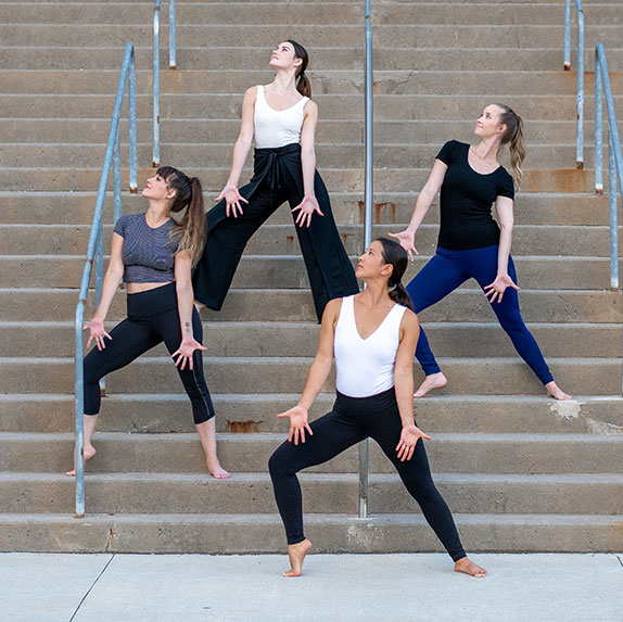 Four women pose on an outdoor staircase