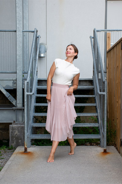 A woman dressed in a white shirt and pink skirt stands in front of a blue staircase